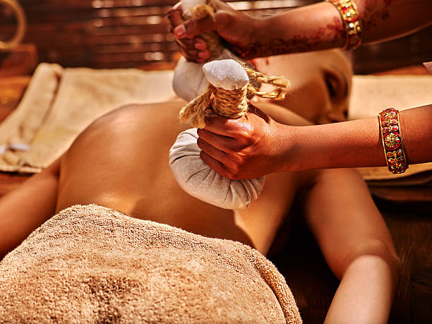 Woman having massage with pouch of rice.​​​ foto