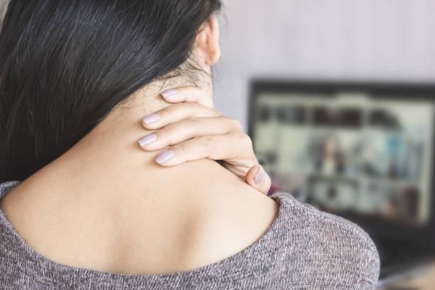 vrouw met nekpijn terwijl het werken op computer laptop - nek stockfoto's en -beelden