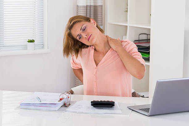 Woman Having Neckache At Desk Young Woman Having Neckache While Calculating Invoice At Desk bad posture stock pictures, royalty-free photos & images