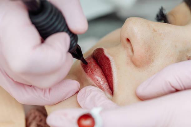 woman having permanent makeup on lips in beauty salon - durabilidade imagens e fotografias de stock
