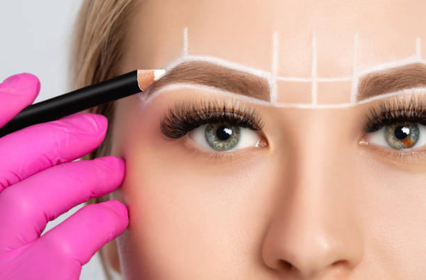 Woman Having Permanent Make-up Tattoo on her Eyebrows. Closeup beautician doing tattooing eyebrow. Green eyes close up. Professional makeup and cosmetology skin care. stock photo