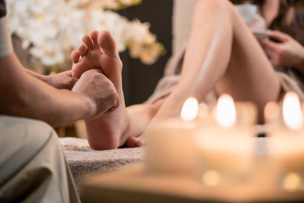 Woman having reflexology foot massage in wellness spa Woman having reflexology foot massage in wellness spa foot massage stock pictures, royalty-free photos & images