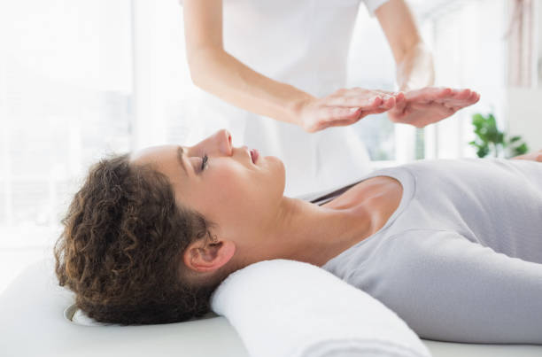 woman having reiki treatment - holistic medicine stock photos and pictures