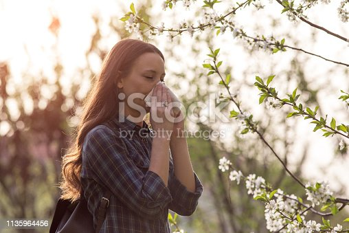 Young pretty girl blowing nose in front of blooming tree. Spring allergy concept