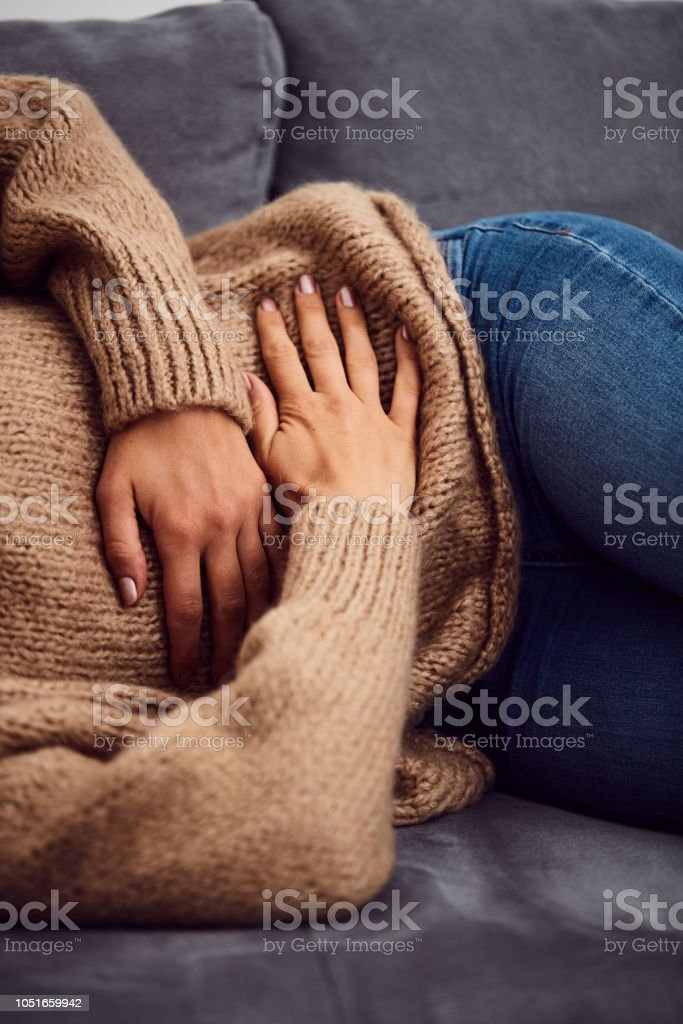 Woman having stomach issues / problems while lying on the couch. stock photo
