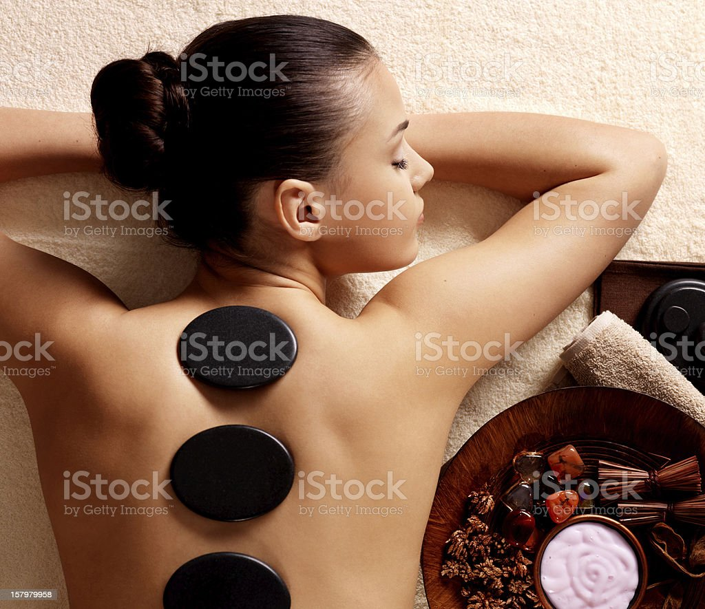 woman having stone massage in spa salon stock photo
