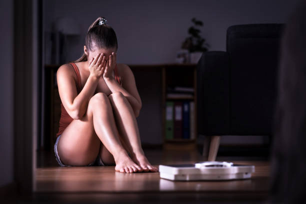 Woman having stress about weight loss, diet or gaining weight. Eating disorder, anorexia or bulimia concept. Young girl crying and sitting on the floor with scale. Woman having stress about weight loss, diet or gaining weight. Eating disorder, anorexia or bulimia concept. Young girl crying and sitting on the floor with scale. Underweight person sad about obesity anorexia nervosa stock pictures, royalty-free photos & images