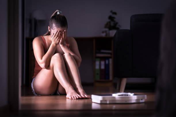vrouw met stress over gewichtsverlies, voeding of het verkrijgen van gewicht. het eten van wanorde, anorexia of boulimia concept. jong meisje te huilen en zittend op de vloer met schaal. - lichaamsbewustzijn stockfoto's en -beelden
