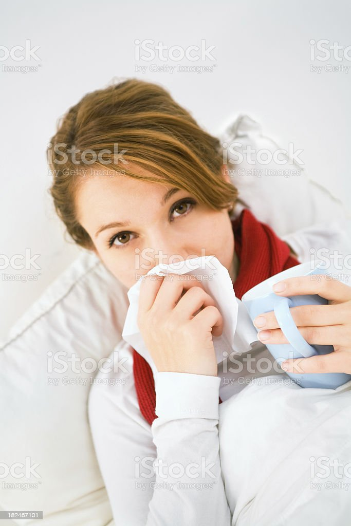 Woman having the flu drinking tea and blowing nose stock photo
