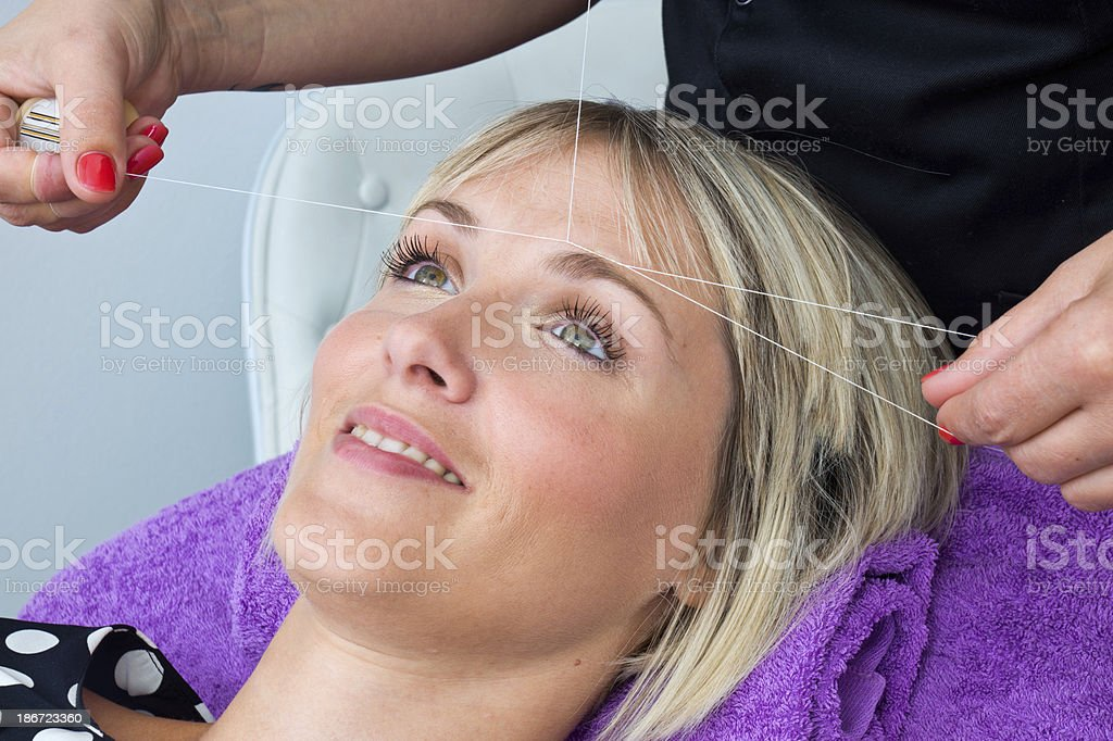 woman having threading hair removal procedure stock photo