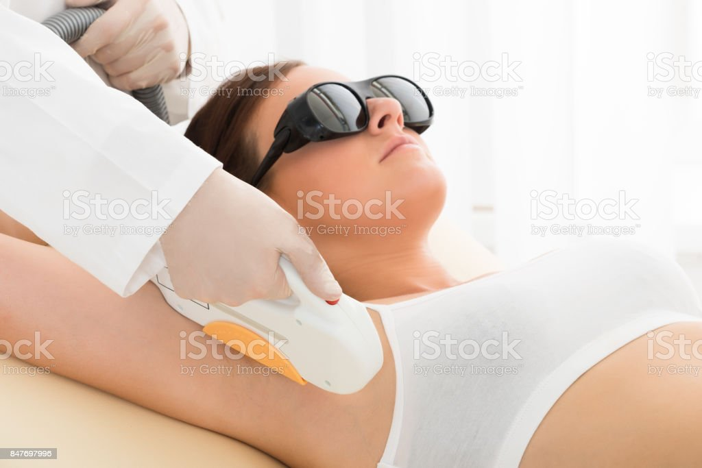 Woman Having Underarm Laser Hair Removal stock photo