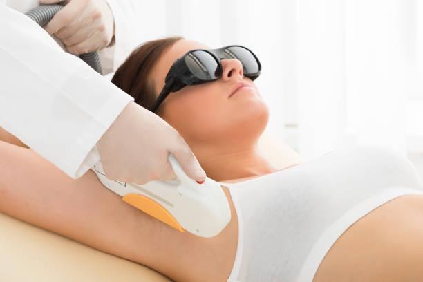 Woman Having Underarm Laser Hair Removal stock photo