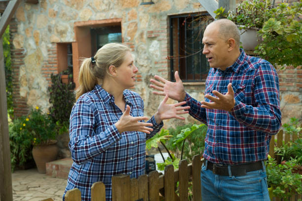 Woman having unpleasant talk with neighbour Worried woman standing behind wooden fence near farmhouse, having unpleasant talk with male neighbour shock tactics stock pictures, royalty-free photos & images