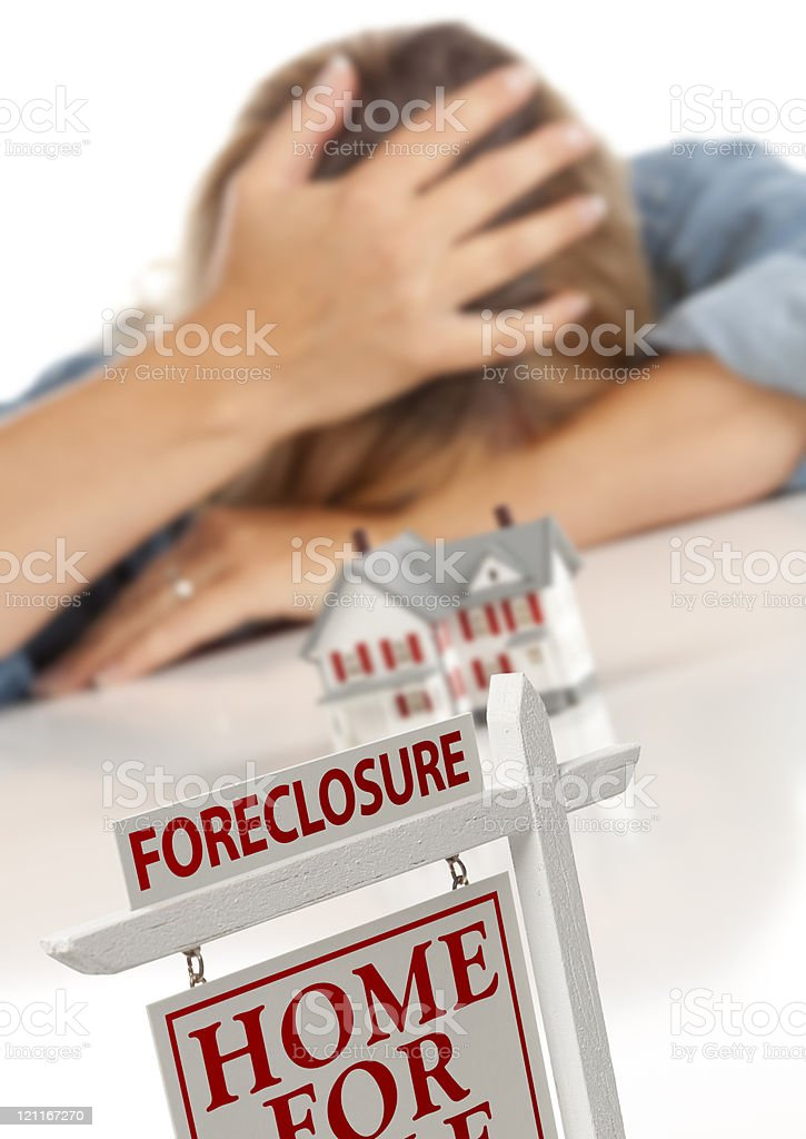 Woman, Head in Hand Behind Model Home and Foreclosure Sign stock photo