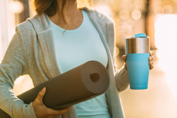 Woman headed to yoga with yoga mat and coffee cup stock photo