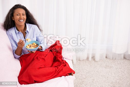 Smiling woman eating cereal with raisins and nuts, sitting on sofa in the living room.