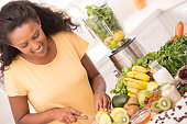 Young beautiful woman preparing lemonade in the kitchen. Close up woman cutting lemons for preparing fresh fruit and vegetable drink.