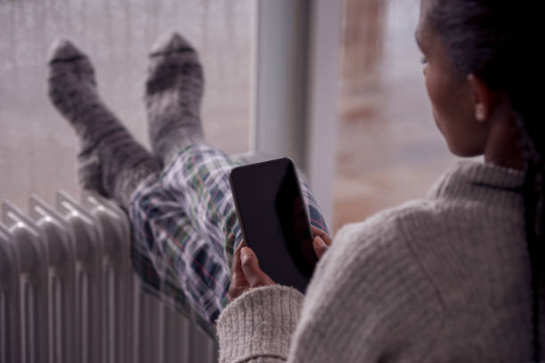 A woman heating up legs in front of an electric heater while using a smartphone. stock photo