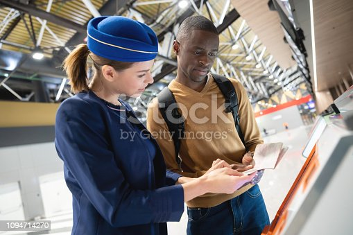 Woman helping a male traveler do the self check-in at the airport using a machine - travel concepts
