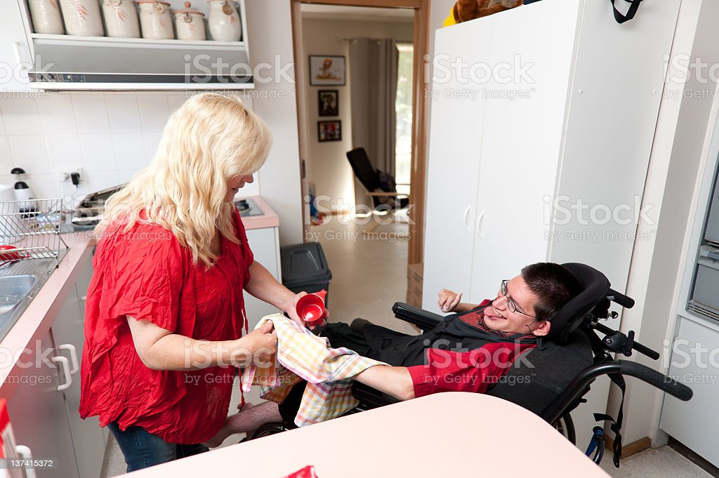 Woman helping a man to dry dishes stock photo