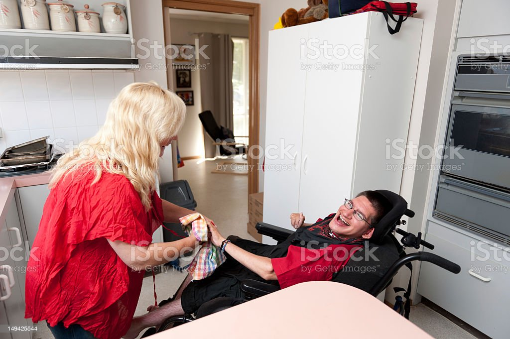 Woman helping a young man to dry dishes stock photo