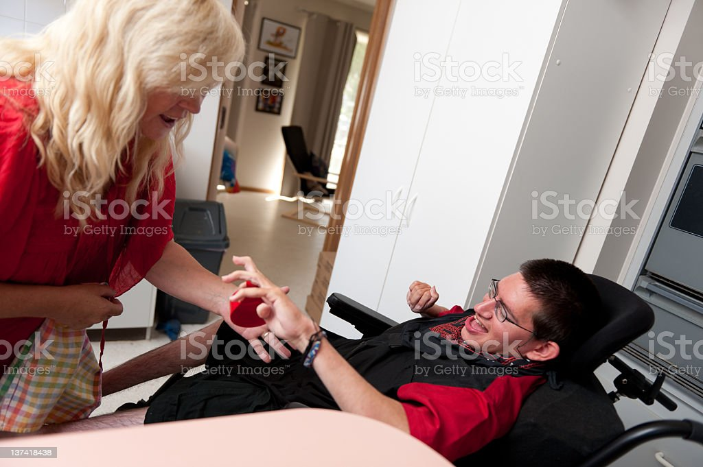 Woman helping a young man to put away dishes stock photo