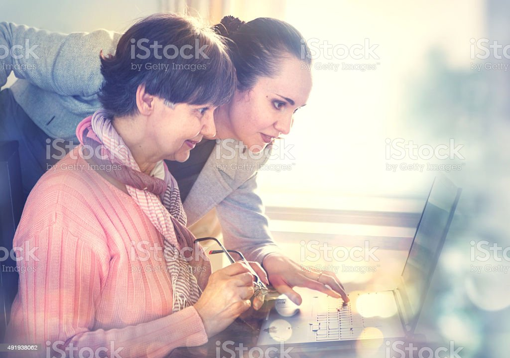 Woman helping an elderly person using laptop for internet search stock photo