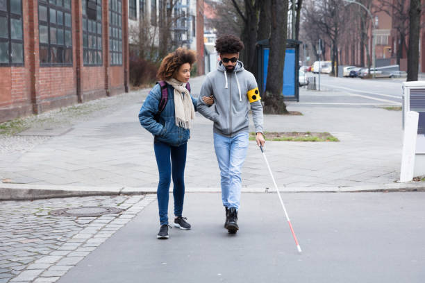 Woman Helping Blind Man While Crossing Road stock photo