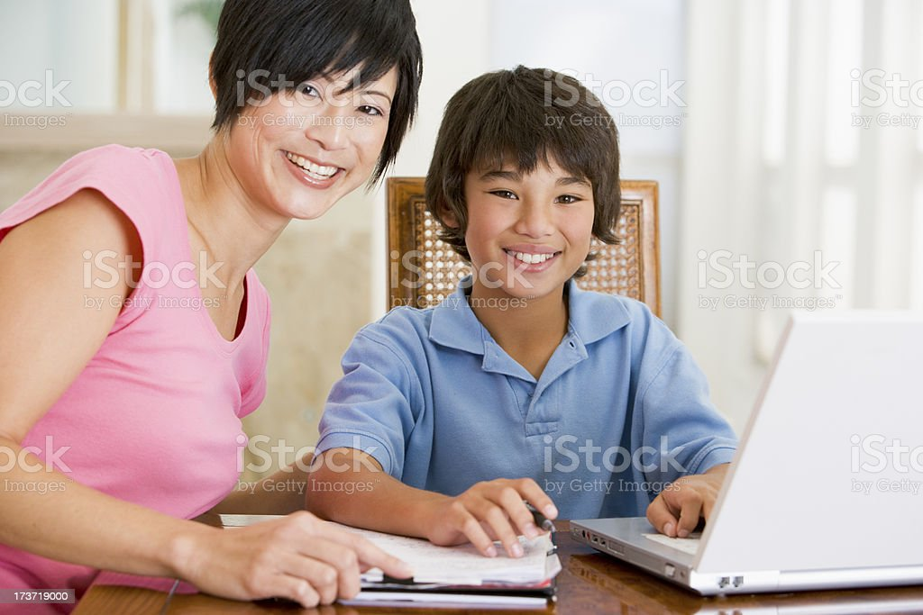 Woman helping boy with laptop do homework in dining room royalty-free stock photo
