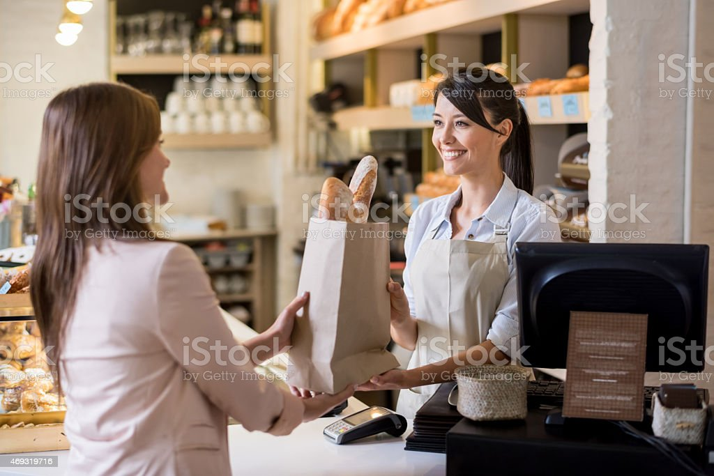 Woman helping customer at the bakery stock photo