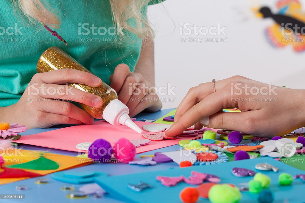 Woman helping girl in making cards stock photo