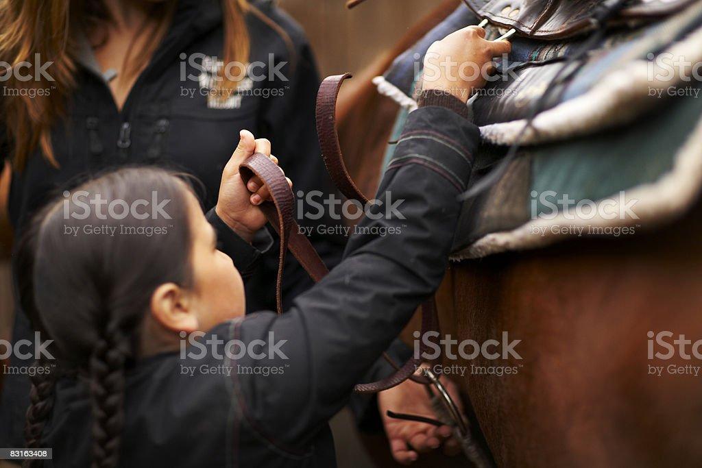 Donna aiutando ragazza sella cavallo foto stock royalty-free