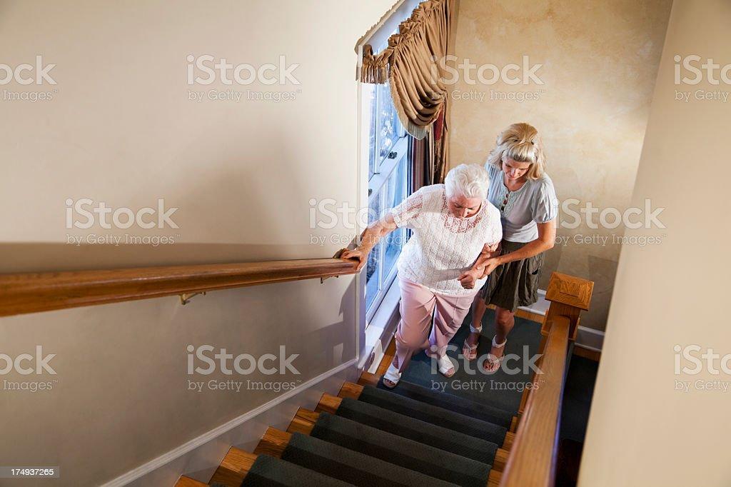 Woman helping grandmother climb stairs stock photo