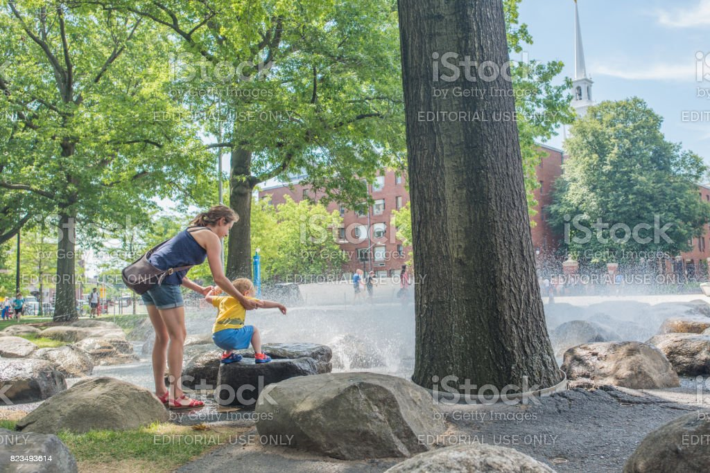 Woman helping her young son climb on the Harvard Campus stock photo