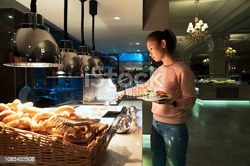 Asian woman helping herself to the breakfast buffet in a luxury hotel's restaurant
