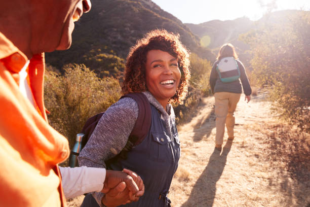 mujer ayudando a hombre en el camino como grupo de amigos mayores van de excursión en el campo juntos - excursionismo fotografías e imágenes de stock