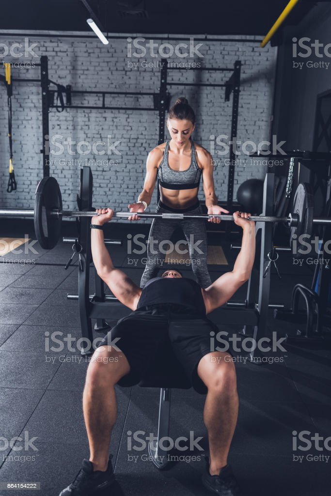 woman helping man to lift barbell royalty-free stock photo