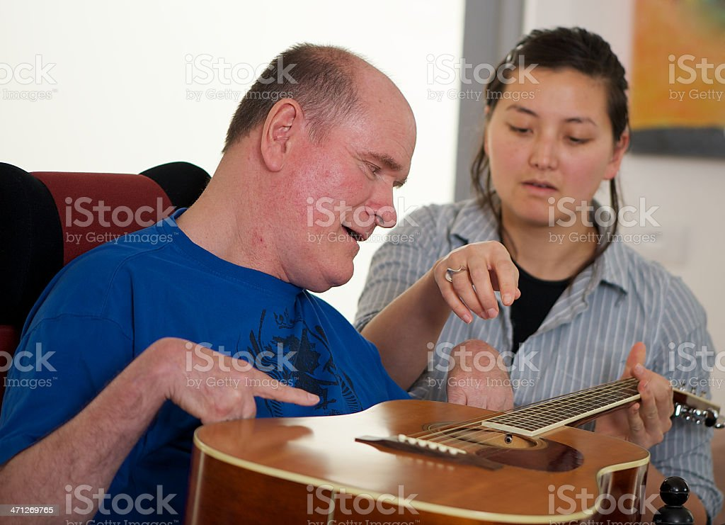 Woman helping man with music therapy stock photo