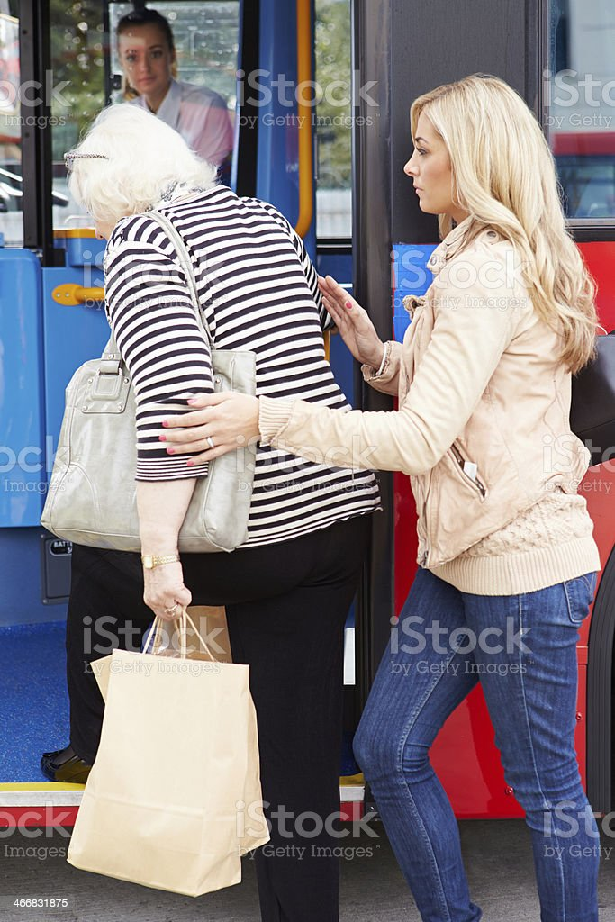 Woman Helping Senior Lady To Board Bus stock photo