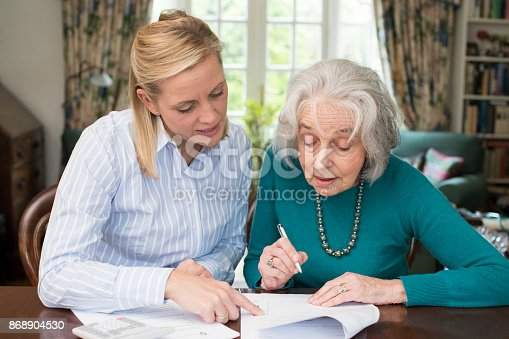 istock Woman Helping Senior Neighbor With Paperwork 868904530