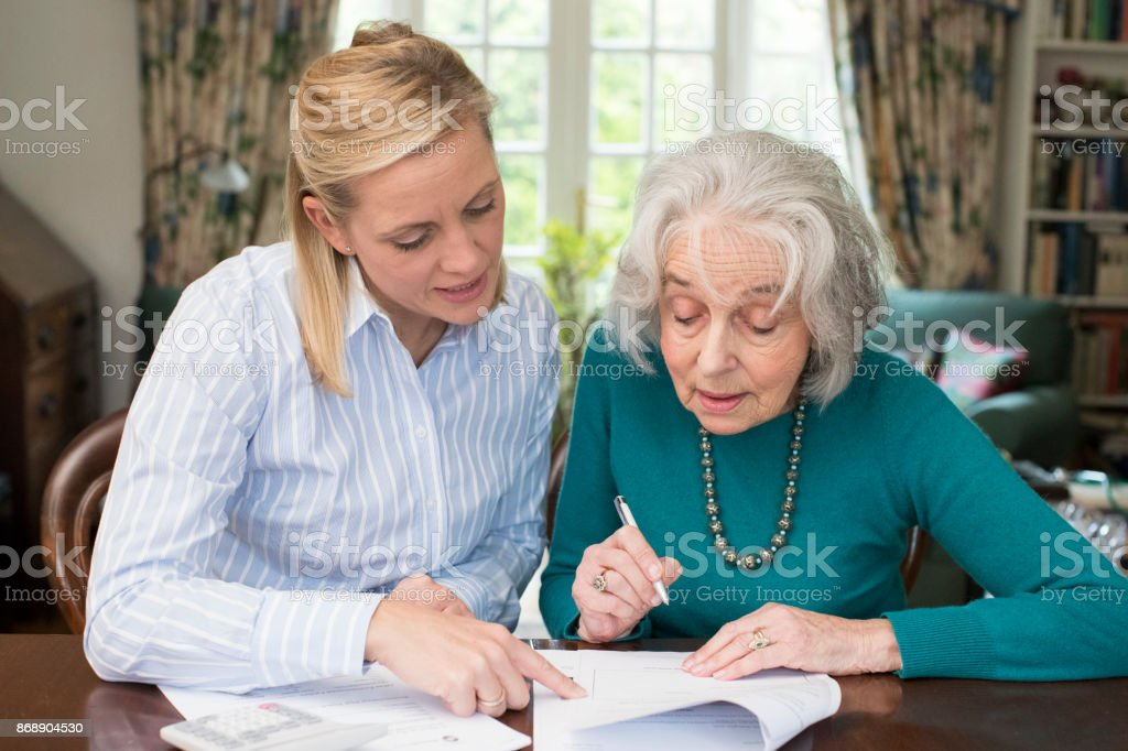 Woman Helping Senior Neighbor With Paperwork stock photo