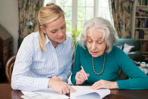 woman helping senior neighbor with paperwork - power of attorney stock pictures, royalty-free photos & images