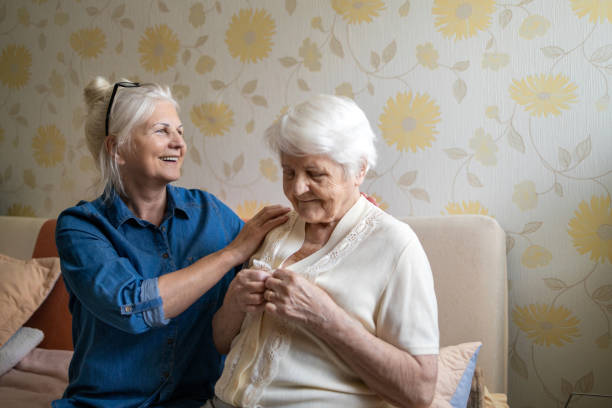 Woman helping senior woman dress in her bedroom stock photo