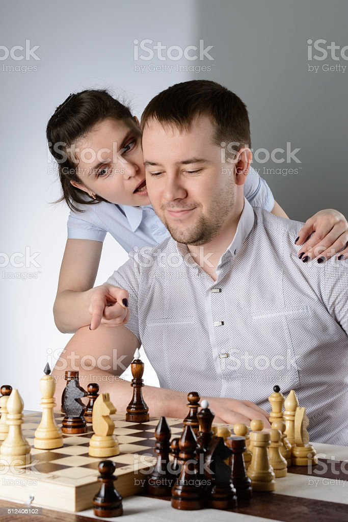 Woman helps a man to play chess stock photo