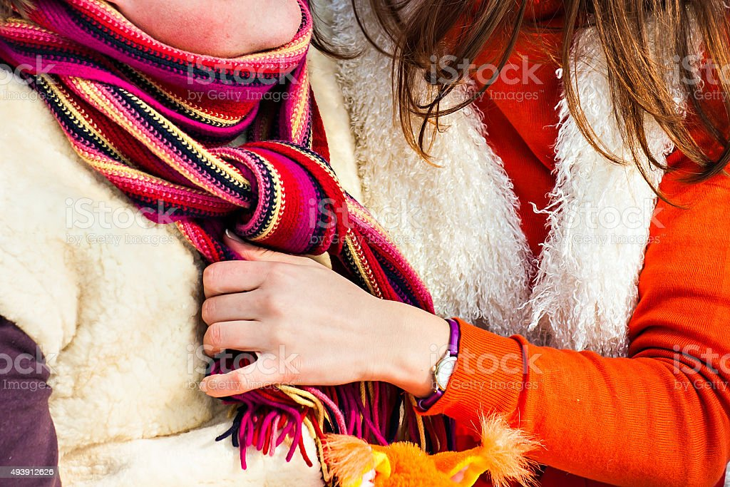 woman helps men to tie a scarf stock photo