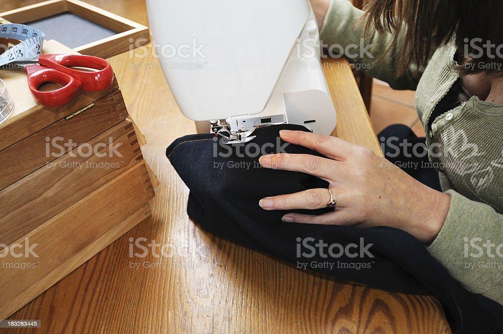 Woman hemming denim jeans royalty-free stock photo