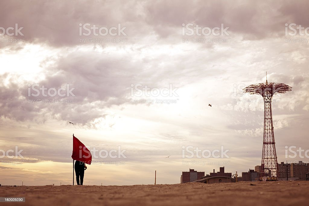 Woman hiding behind a flag on Coney Island royalty-free stock photo
