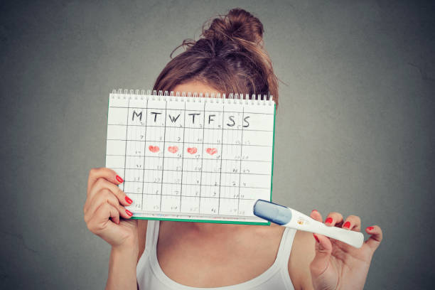 woman hiding behind a periods calendar and showing a positive pregnancy test stock photo
