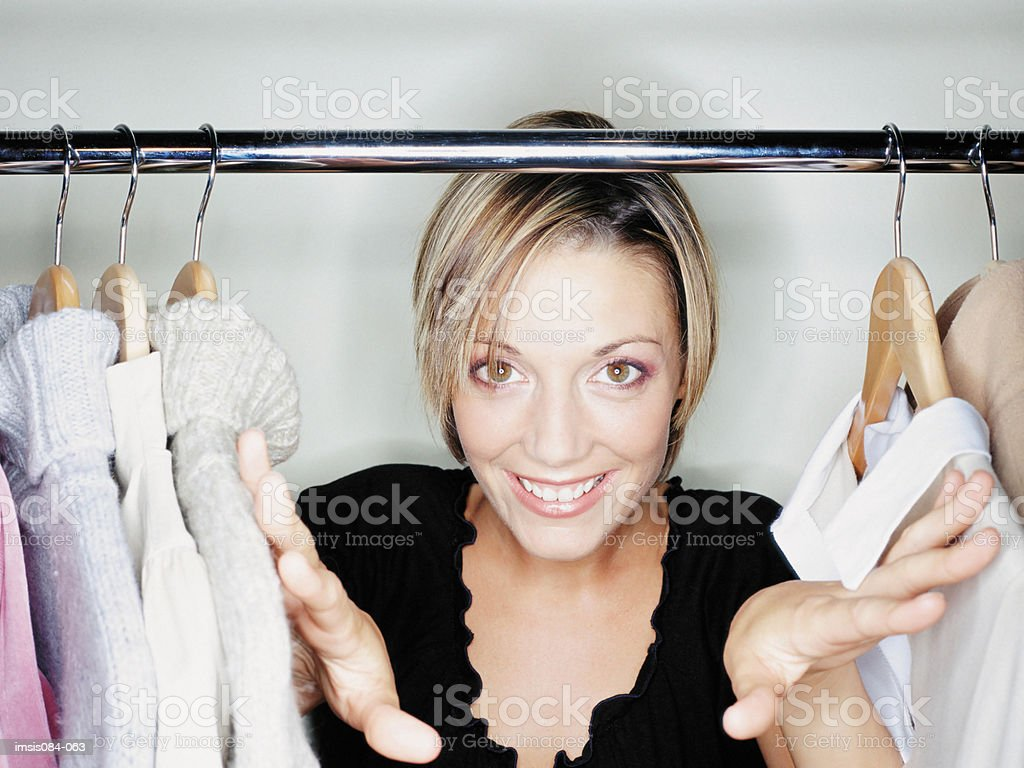 Woman hiding behind clothes royalty-free stock photo