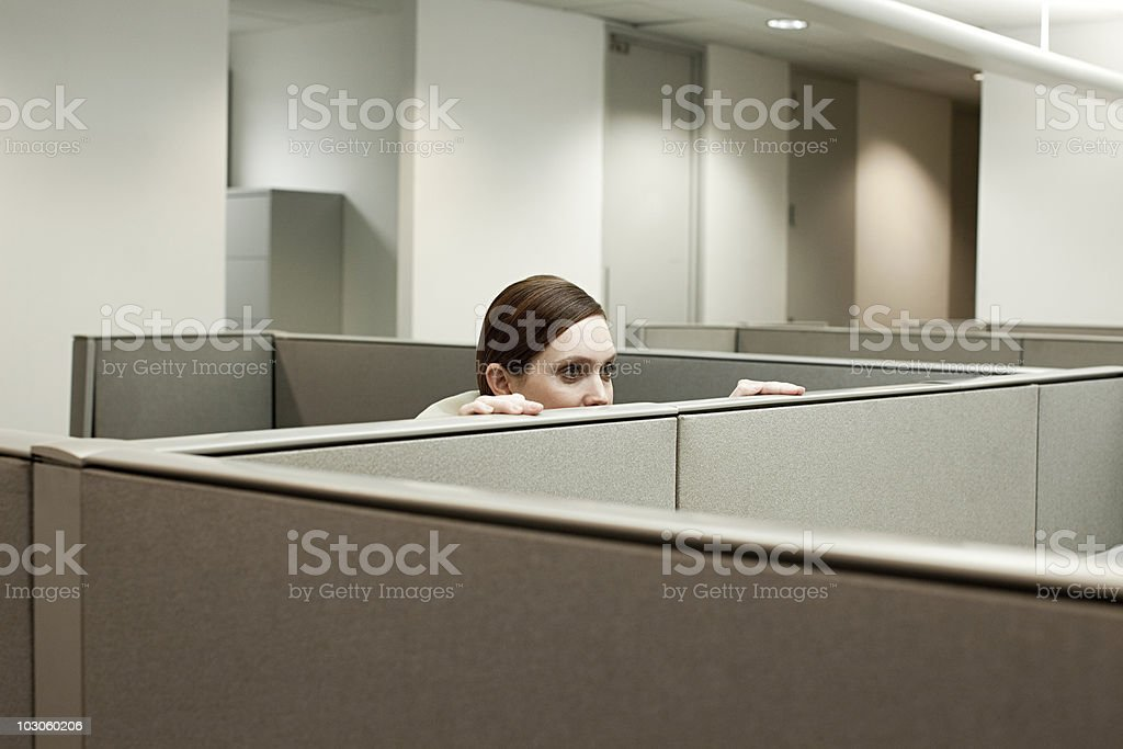 Woman hiding behind cubicle in office stock photo